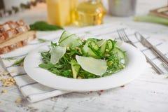 Insalata verde vegetariana con i dadi dell'avocado della rucola del parmigiano Immagine Stock