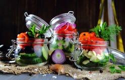 Insalate dei pomodori freschi, cetrioli in barattoli di vetro Fotografia Stock