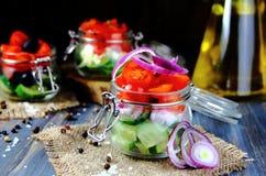 Insalate dei pomodori freschi, cetrioli in barattoli di vetro Fotografie Stock