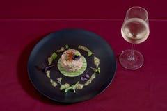 Insalate di rinfresco con il pesce, che può essere servito per la prima colazione, il pranzo o la cena PLATd VERDE e NERO per la  Fotografia Stock