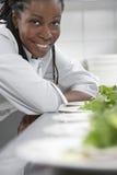 Insalate femminili di With Plates Of del cuoco unico in cucina fotografie stock