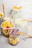 Insalate saporite delle verdure in barattoli con mais ed i germogli sul tavolo da cucina rustico leggero, fine su Fotografia Stock