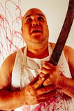 Insane bloody butcher. Crazy insane butcher covered with blood.  Harsh lighting for more disturbing feel Stock Images