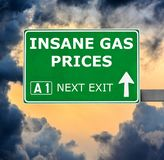 INSANE GAS PRICES road sign against clear blue sky royalty free stock photo