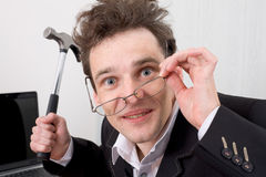 The insane man with a hammer in a hand. The businessman in spectacles gone mad with a hammer in a hand Royalty Free Stock Photos