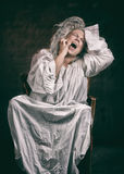 Insane woman. Studio portrait of a screaming crazy woman, dark background Royalty Free Stock Photo