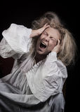 Insane woman. Studio portrait of a screaming crazy woman, dark background Royalty Free Stock Photos