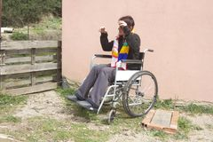 Insane woman on wheelchair. Insane woman moving on wheelchair royalty free stock photography