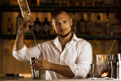 Insanely young man prepares mixed drinks for his guests. royalty free stock image