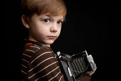 Insant camera kid. Young child holding a instant camera on a white background Royalty Free Stock Photography