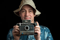 Insant camera man. Man holding a instant camera on a white background Stock Photography