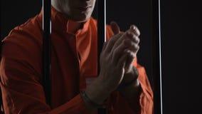 Insasse in den Handschellen, die Handgelenke, unmenschliche Bedingungen und Folterungen im Gefängnis reiben stock footage