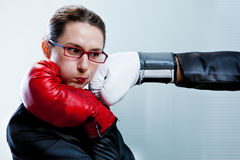 Inscatoli il guanto che colpisce il fronte di una donna di affari Fotografie Stock Libere da Diritti