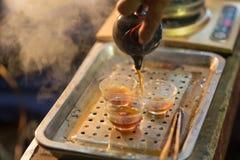 Inschenkend hete Chinese thee aan een uiterst kleine theekoppen Stock Afbeelding