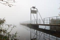 Inschepend pijler voor het eiland van Virginia, meer Varese, Biandronno, Italië, op een koude en nevelige de herfstochtend Stock Afbeelding