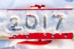 Inschrijving 2017 door sneeuw op de schommeling van de rode kinderen Stock Afbeeldingen