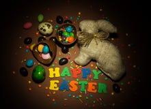 Inschrijving Gelukkige Pasen, Konijntje, paaseieren, chocolade, dragees stock afbeelding