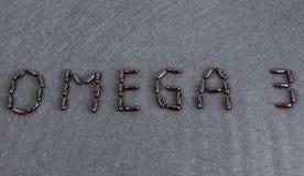 Inschrijving Omega 3 op zwarte achtergrondgelcapsules stock afbeelding