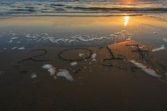 Inschrijving 2017 op een zandig strand tijdens zonsondergang Stock Afbeeldingen