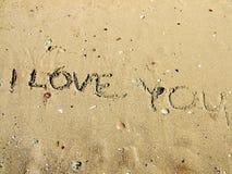 Inschrijving op het strandzand over liefde Stock Afbeeldingen