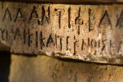 Inschrijving op oud graf in de Griekse taal Karakters, symbolen hiërogliefen royalty-vrije stock fotografie