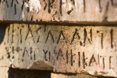 Inschrijving op oud graf in de Griekse taal Karakters, symbolen hiërogliefen royalty-vrije stock afbeeldingen