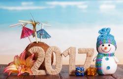 Inschrijving 2017, raad, sneeuwman en Kerstmisklatergoud op een achtergrond van overzees Stock Afbeelding