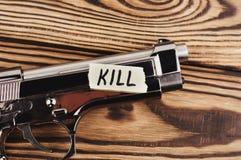 Inschrijvingsdoden op gescheurd document en glanzend pistool stock fotografie