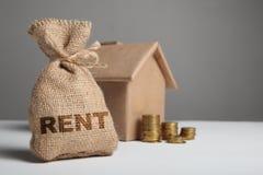 Inschrijvingshuur op uitstekende zak geld tegen achtergrond van huiscijfer en stapel gele muntstukken Koop en huurprijs royalty-vrije stock afbeeldingen