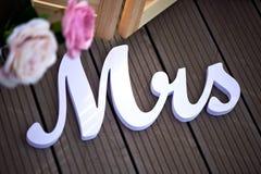 Inschrijvingsmevr. als decor bij het huwelijk tegen de donkere raad met roze bloemen Royalty-vrije Stock Foto's