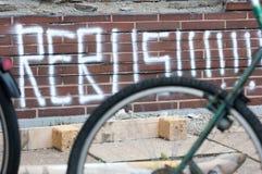Inschrijvingsrebus op een bakstenen muur door het wiel van een fiets royalty-vrije stock fotografie