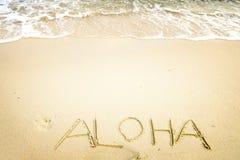 Inscrição Aloha escrita no Sandy Beach com onda de oceano Imagem de Stock