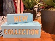 Inscrição - coleção nova em uma loja de roupa imagens de stock royalty free