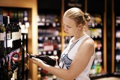 Inscrição da leitura da mulher na garrafa de vinho dentro Fotos de Stock