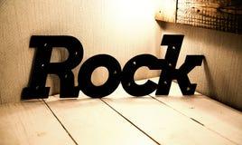 Inscrição da rocha na tabela de madeira Fotografia de Stock Royalty Free