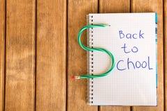 Inscrição de volta à escola no bloco de notas no fundo de madeira fotos de stock royalty free
