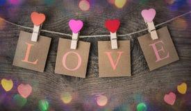 A inscrição do amor e os grampos vermelhos do coração que penduram no cabo natural para Valentine Day Imagens de Stock Royalty Free