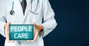 Inscrição do cuidado dos povos do doutor Holding Tablet With na tela Tecnologia moderna no conceito da medicina com Cópia-espaço Imagem de Stock Royalty Free