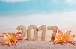 Inscrição 2017 do Natal na areia decorada com flores tropicais em um fundo do mar Imagens de Stock