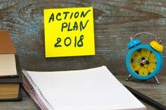 Inscrição 2018 do plano de ação escrita na nota pegajosa Livros, pena, Fotografia de Stock Royalty Free