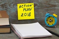 Inscrição 2018 do plano de ação escrita na nota pegajosa Livros, pena, Foto de Stock