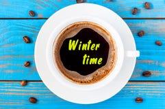 Inscrição do tempo de inverno na caneca da manhã de café ou de latte quente na tabela de madeira azul imagem de stock