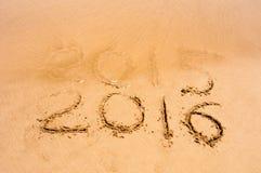 A inscrição 2015 e 2016 em uma areia da praia, a onda está começando cobrir os dígitos 2015 Imagens de Stock Royalty Free