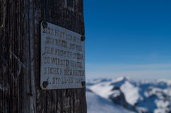 Inscrição em uma cruz nas montanhas, Kleinwalsertal da cimeira, Áustria Foto de Stock Royalty Free