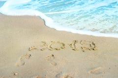 inscrição 2019 escrita no Sandy Beach com aproximação da onda imagem de stock