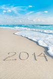 A inscrição 2014 na praia da areia do mar com o sol irradia Foto de Stock Royalty Free