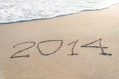 A inscrição 2014 na praia da areia do mar com o sol irradia Imagem de Stock Royalty Free