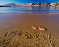 Inscrição na praia, escudo real do feriado Foto de Stock