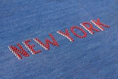 Inscrição New York do close up, cristais de rocha embutidos na sarja de Nimes Imagem de Stock Royalty Free