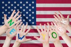 Inscrição New York nas mãos das crianças na perspectiva de uma bandeira de ondulação dos EUA imagens de stock